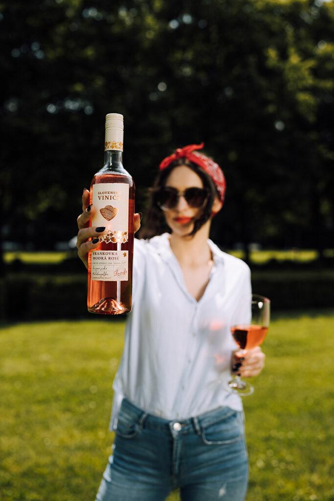 Žena drží v ruke ružové víno Slovenské vinice